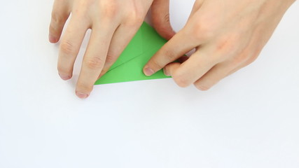 hands of guy make origami crane on white background, time lapse