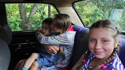 two sisters with brother sit in back seat car, then machine goes