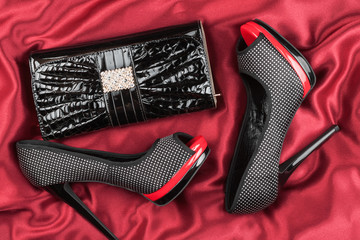Shoes and bag  lying on red fabric