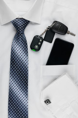 Phone  lying on the shirt  and tie