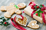 Christmas gift box and gingerbread cookies on wooden background poster