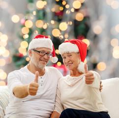 happy senior couple in santa helper hats