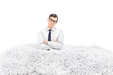 Displeased man standing in a pile of shredded paper