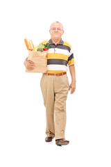 Senior walking with a bag of groceries