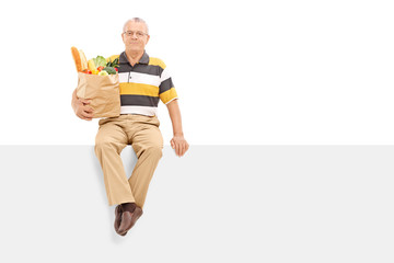 Senior holding bag with groceries seated on panel