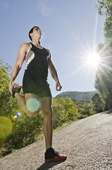 Runner warming legs with sun flare