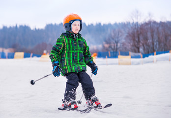 Young skier slide down from snow hill
