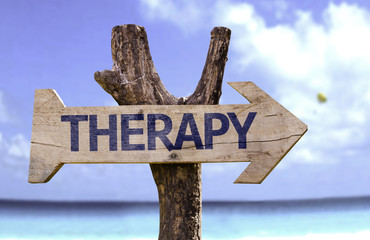 Therapy wooden sign on a beach background