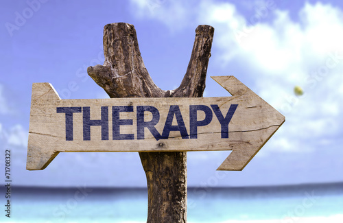Leinwanddruck Bild Therapy wooden sign on a beach background