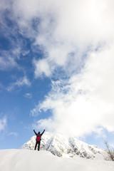 Uomo con braccia in alto in montagna d'inverno con ciaspole
