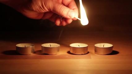 Lighting a line of Tea Candles