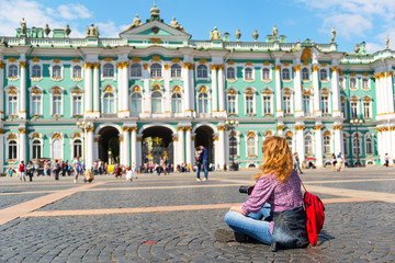 Young female tourist in front of the Winter Palace in St. Peters