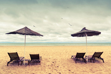Sunbeds and umbrellas on empty sandy beach. Instagram toned phot
