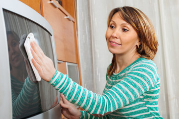 woman in green cleaning TV with rag