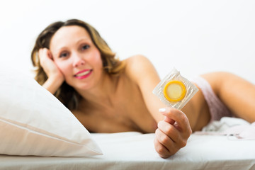 woman showing condom on the bed. Focus on condom