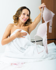 Middle-aged woman undressing in bed