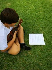 boy playing the ukulele on the grass in Hawaii