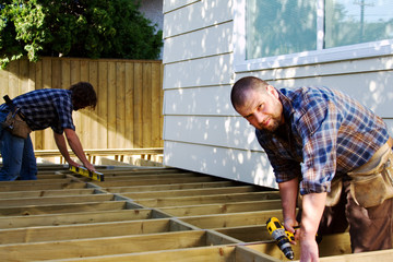 Two carpenters building a deck