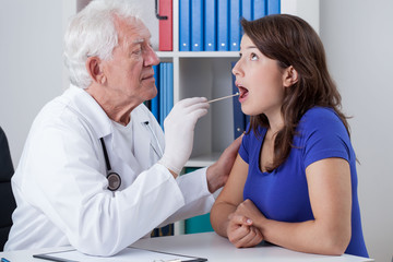 General practitioner examining throat