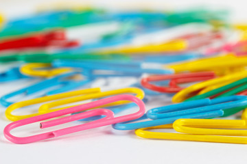 Bright multicolored office paperclips close up