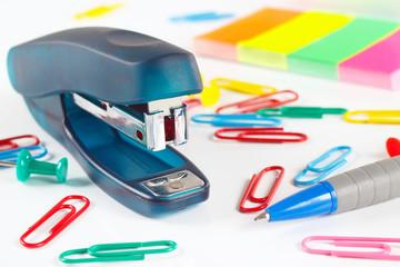 Stapler and multicolored stationery on white desktop