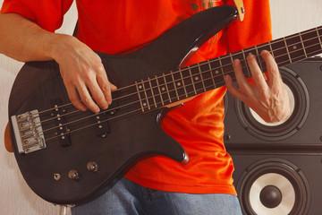 Posing hands of rock musician playing the bass guitar