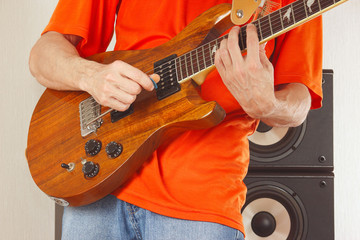Hands of man put guitar chords closeup