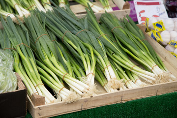 a crate of spring onions at a market.