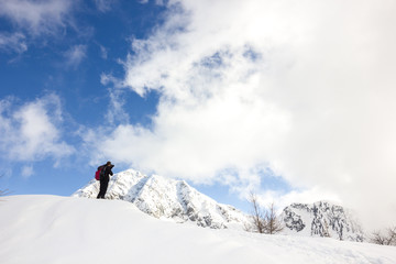 Uomo fotografa montagna in inverno con neve