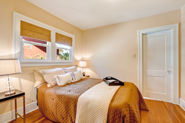 Warm bedroom interior with brown bedding and ivory blanket