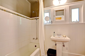 Bathroom with plank paneled wall and tile trim
