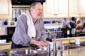 Elderly man washing dishes