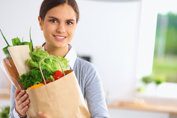 Happy young  woman with shopping bag full of vegetables