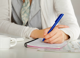A woman at the desk write on a paper, isolated on white.