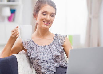 Beautiful smiling young woman with laptop and cup of coffee on
