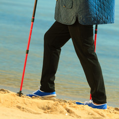 active woman senior nordic walking on a beach. legs
