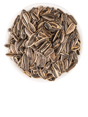 Sunflower seeds in white bowl over white background