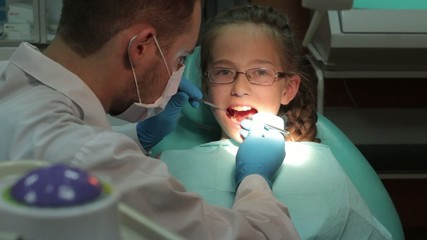 Dentist carry out routine inspection of the patient
