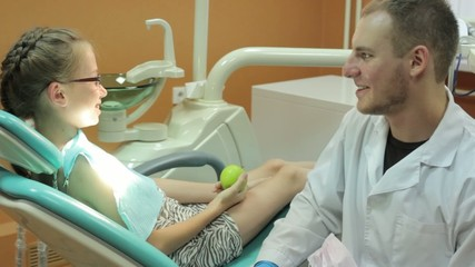 Dentist gives green apple little girl after treatment