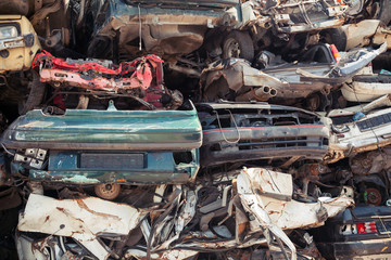 Abstract background with dump of stacked cars in junkyard