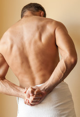 Back of Strong young Caucasian man with white towel