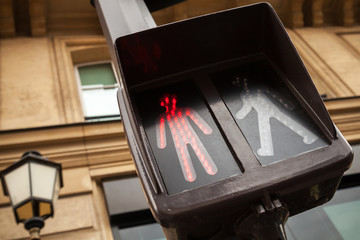 Pedestrian crossing traffic lights show red stop signal