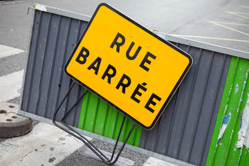 French road barrier with closed street roadsign