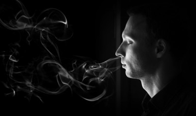 Closeup profile portrait of young man with closed eyes and smoke