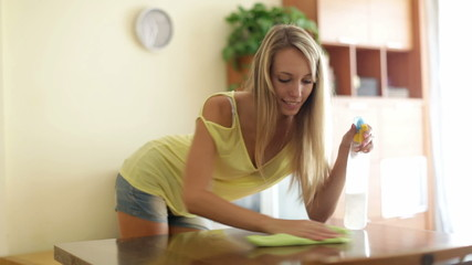 girl  dusting furniture with detergent polish at home