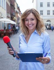 Frau mit blonden Locken macht eine Umfrage auf der Strasse