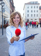canvas print picture - Frau mit blonden Locken interviewt einen Passanten