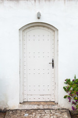 White wall and old wooden door. Background texture