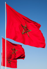 National flags of Morocco above clear blue sky