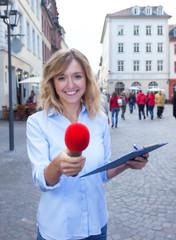 Frau mit blonden Locken interviewt einen Passanten